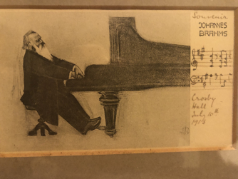 Postcard of Brahms playing piano.