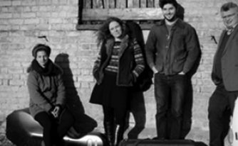 Black and white photograph of the members of the Allegri Quartet in front of a brick building